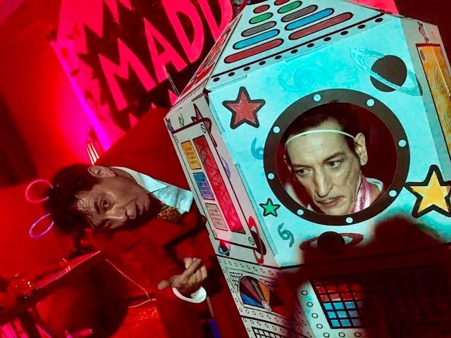 Maynard onstage with Lance Leopard inside the cardboard love rocket.